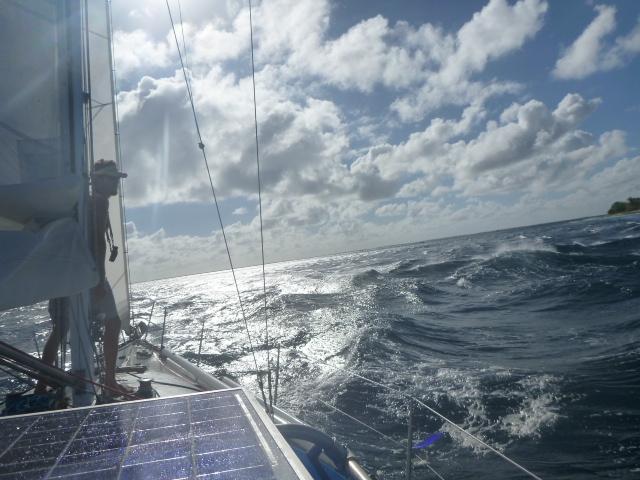 sailing through waves in tuamotus on the horizon line bri and rob travel and sailing adventure