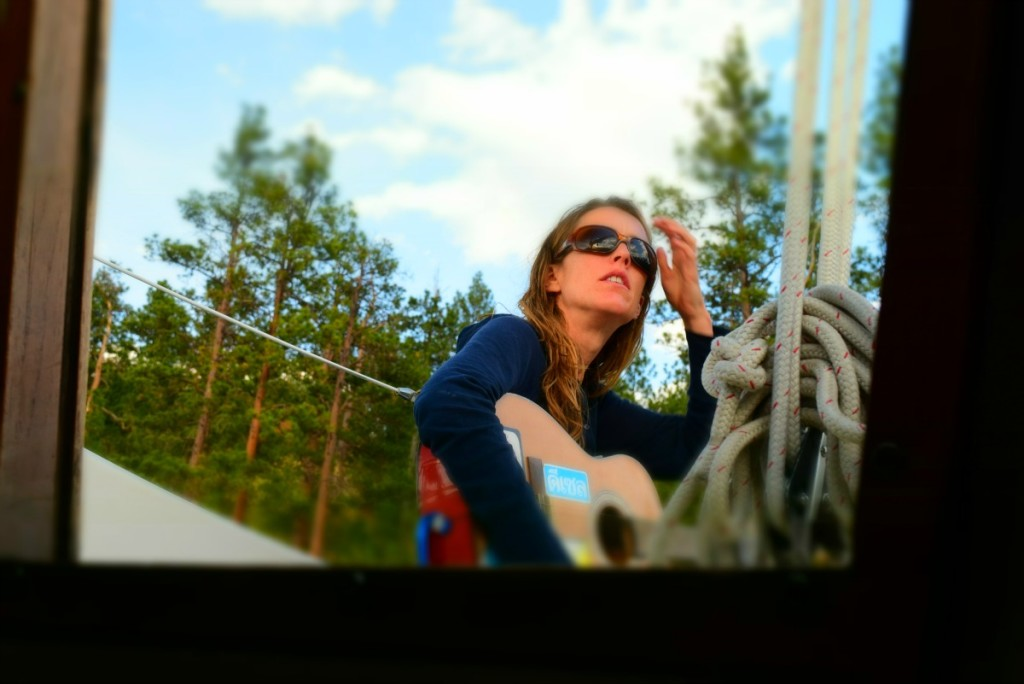 Brianna Randall playing guitar onboard a sailboat in Montana